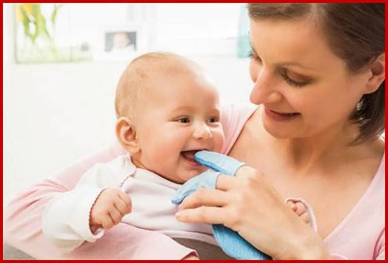 Một trong những mẹo cho bé chậm mọc răng là xoa nướu